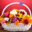 Royalty-Free Stock Photo: Beautiful bouquet of bright flowers in white basket on wooden table on pink