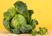 Fresh savoy cabbage on wooden table on yellow background — Stock Photo
