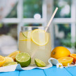Citrus lemonade in glass bank of citrus around on blue wooden table on wind — Stock fotografie