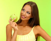 Beautiful young woman with green apple, on green background — Stock fotografie