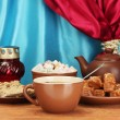 图库照片: Teapot with cup and saucers with oriental sweets - sherbet, halva and turki