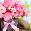 Bouquet of eustoma flowers in wicker vase, on wooden table, on green backg — Stock Photo #13649163
