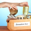 Donation box with food on blue background close-up — Stock Photo #13649218
