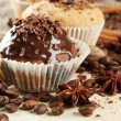 Tasty muffin cakes with chocolate, spices and coffee seeds, on beige backgr — Stock Photo #13649851