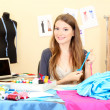 Beautiful young dressmaker in workroom - Stock Photo