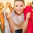 Beautiful young woman near rack with hangers — Stock Photo #13649910