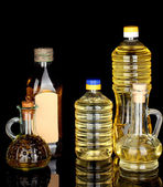 Olive and sunflower oil in the bottles and small decanters isolated on blac — Stock Photo