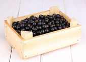 Black currant in crate on wooden background — Stock Photo
