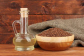 Linseed oil with flax seeds on wooden background close-up — Stok fotoğraf