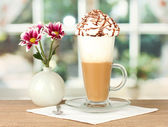 Glass of fresh coffee cocktail and vase with flower on wooden table close-u — Stock Photo