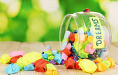 Glass vase with paper stars with dreams on wooden table on natural backgrou — Stock Photo