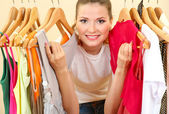 Beautiful young woman near rack with hangers — Foto Stock
