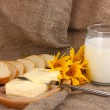 Butter on wooden holder surrounded by bread and milk on sacking background — Stock Photo #13650184