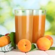 Glasses of apricot juice and fresh apricots on white wooden table on green — Stock Photo #13651033