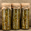 Glass jar with tinned capers on sack background close-up - Stock Photo