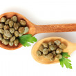 Green capers in wooden spoons on white background close-up - Stock Photo