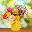 Bright yellow bucket with flowers on green background - Stock Photo