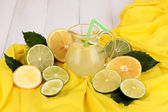Citrus lemonade in glass pitcher of citrus around on yellow fabric on white — Stock Photo