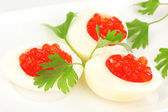 Red caviar in eggs on white plate close-up — Stock Photo