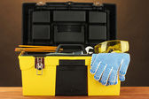 Open yellow tool box with tools on brown background close-up — Stock Photo