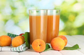 Glasses of apricot juice and fresh apricots on white wooden table on green — Stock Photo