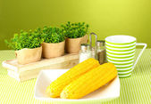 Boiled corn and flowers on a green background — Stock Photo