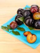 Rip prunes sur le panier sur la table en bois — Photo