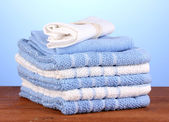 Kitchen towels on wooden table on blue background close-up — Stock Photo