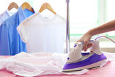 Woman hand ironing a shirt, on cloth background — Foto de Stock