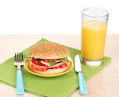 Apetyczne kanapki na tabliczce koloru na drewnianym stole na białym tle — Zdjęcie stockowe
