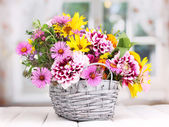 Beautiful bouquet of bright flowers in basket on wooden table — Stock Photo