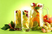 Jar and glasses with citrus fruits and raspberries, on green background — Stock Photo