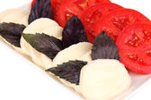 Tasty mozzarella with tomatoes on plate close-up — Stock Photo