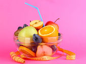 Glass bowl with fruit for diet and measuring tape on pink background — Stock Photo