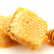 Golden honeycombs and wooden drizzler with honey isolated on white — Stock Photo #13664496