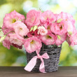 Bouquet of eustoma flowers in wicker vase, on wooden table, on green backg — Stock Photo