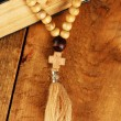 The Wooden rosary beads and holy bible on wooden background close-up - Stock fotografie