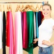 Beautiful young woman near rack with hangers - ストック写真