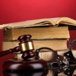 Gavel, handcuffs and book on law on red background - Stock Photo