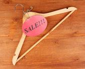 与销售标记木制背景上的衣架 — 图库照片
