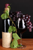 Bottle of wine with grape leaves on wooden table on black background — Stock Photo