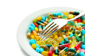 Colorful capsules and pills on plate with fork, isolated on white — Stock Photo