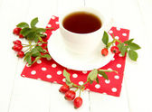 Cup of tea with hip roses, on wooden table — Stock Photo