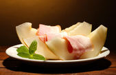 Parma ham and melon, on wooden table, on brown background — Stock Photo