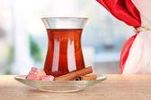 Kieliszek tureckiej herbaty i rahat lokum, na drewnianym stole — Zdjęcie stockowe