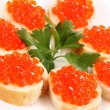 Red caviar on bread on white plate close-up - Stock Photo