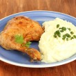 Roasted chicken leg with mashed potato in the plate on wooden table close-u — Stock Photo #13692692
