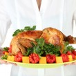 Chef holding a plate of baked chicken with vegetables close-up — Stock Photo #13693113