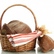Tasty rye breads with ears in basket, isolated on white - Foto Stock