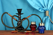 Hookah on a wooden table on a background of blue curtain close-up — Stock Photo